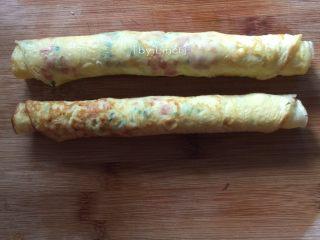 火腿蒜香鸡蛋卷,趁有温度时轻轻卷成卷,尽量卷紧一点哦,不然易松散开来