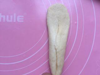黄油面包卷,拿一个放平,收口朝上。用擀面杖从中间先往上擀开。