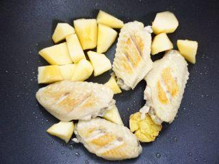 鹰嘴豆焖鸡翅,鸡翅煎好一面后,翻面,再把苹果也一齐放入煎香一下。