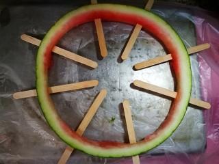 西瓜冰糕,先前切好的西瓜皮用小刀切小口,插好冰糕棍,如图,八支哦。找好盘子铺上保鲜膜,摆好西瓜皮,因为倒入液态要直接入冰箱冷冻的。