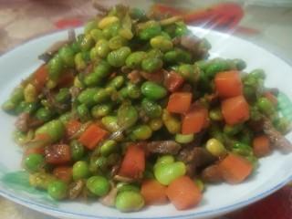 毛豆小炒,将菜装上盘子。就着大米饭吃,是老人和孩子喜爱的菜。豆软胡萝卜面,散发香气。