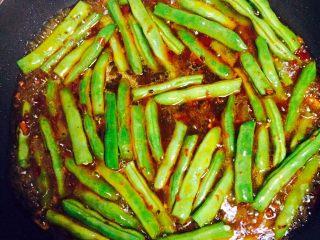 四季豆烧茄子,倒入四季豆,翻炒均匀后加入小半碗水,刚好淹没完四季豆