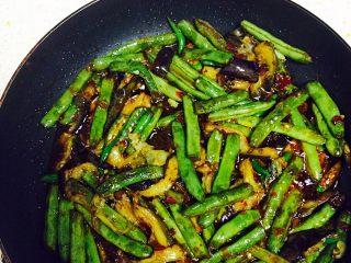 四季豆烧茄子,四季豆煮熟以后倒入青椒和茄子,小火翻炒