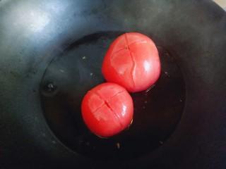 番茄龙利鱼汤,把番茄切十字刀,放入沸水锅中煮2分钟捞出。