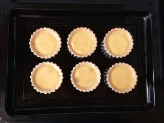 玉米奶酪蛋挞,将蛋挞模放入烤盘中,再倒入挞水,约八分满。烤箱预热后,用180℃上下火烘烤二十分钟直至挞水凝固。