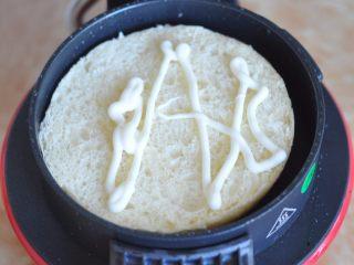 蔬菜总荟汉堡,将事先做好的汉堡胚横切开。早餐机先预热几分钟,然后将底片的面包片放入早餐机底部,挤上沙拉酱。