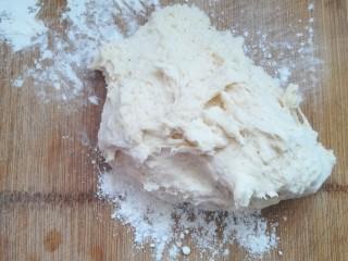 包菜馅素包子,案板上洒些干面粉,把面团移至案板上。