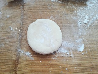 包菜馅素包子,取一个面剂子按扁。