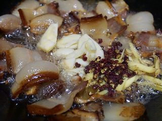干锅茶树菇,待肉片打卷时下大蒜,老姜,豆瓣酱,花椒粒爆香锅