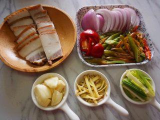 干锅茶树菇,将腊肉切成均匀的薄片,洋葱切成块,辣椒切成斜刀片,大蒜拍碎,老姜切成丝,葱切成段待用