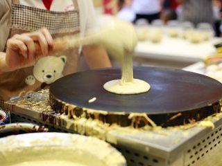 天津老味煎饼果子,当煎饼果子铛温热时,盛一汤勺满眼黄绿色的绿豆面糊倒在铛上。