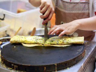 天津老味煎饼果子,用小铲子利落地从中间切一刀
