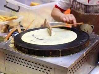"""天津老味煎饼果子,用""""竹蜻蜓""""刮子以铛的中心为圆心轻轻划几圈"""