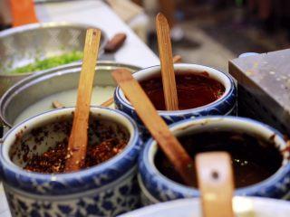 天津老味煎饼果子,辅助食材除了三大酱即天津甜面酱、腐乳酱汁、辣椒酱外还有小香葱和黑(白)芝麻。 腐乳酱汁就是用腐乳的原汁将腐乳块稀释。 辣椒酱是由辣椒粉和辣椒面油炸而成的。