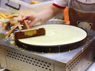 天津老味煎饼果子,一直画到铛的边缘,瞬间薄如蝉翼的一张煎饼就摊成了。
