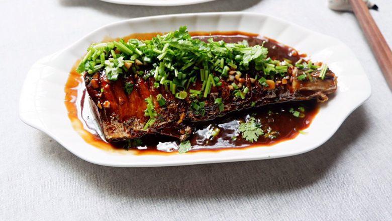 蒜香烧鲅鱼尾,把勾好芡的汤汁浇到鱼身上,撒葱花香菜,就可以开动了。