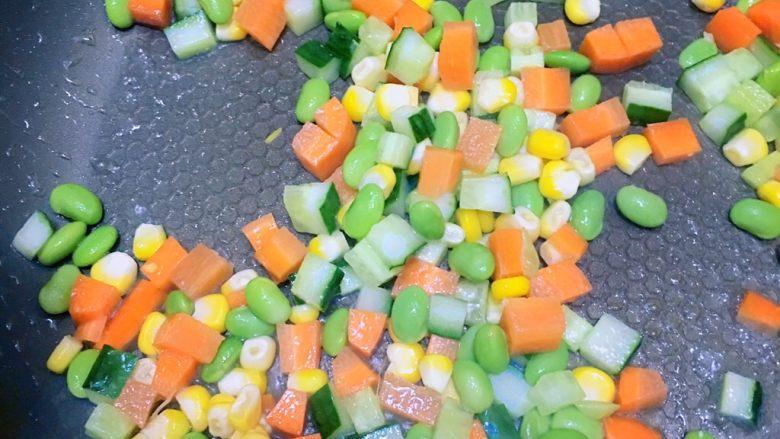食疗-鸡胸肉减脂食谱,倒入油,热油后倒入胡萝卜丁,黄瓜丁,玉米粒,青豆粒,翻炒至香,再倒入已炒好的鸡蛋,盛出