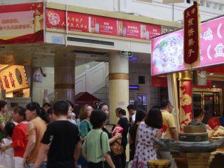 天津老味煎饼果子,天津南市食品街的煎饼果子摊一共有四个摊位,东西南北门各有一个摊位,这是游客们买煎饼果子排队的情景。
