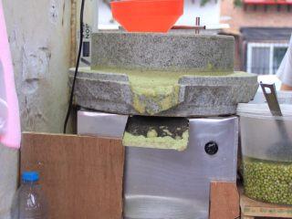 天津老味煎饼果子,这是小石磨,居民楼群里摊位大多使用这种小石磨。图中右下方的桶里放的是泡好的绿豆。