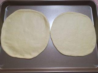 鲜虾火腿披萨,4.将面团拿出来排气,平均分成两份,滚圆,盖上保险木松弛15分钟,用擀面杖将面团擀成两个八寸的圆形。用手调整一下,圆形外圈比中间厚一些。