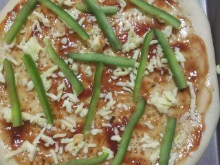 鲜虾火腿披萨,涂好酱后撒上一些马苏里拉芝士碎,放上青椒。