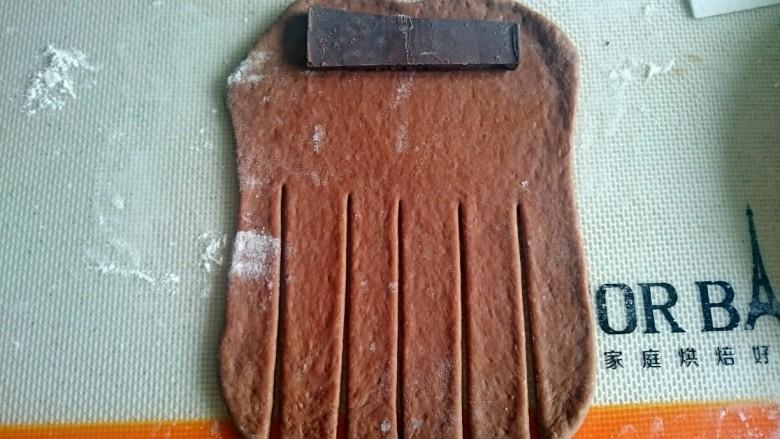 巧克力毛毛虫面包,松弛以后,在揉面垫上撒点高粉,把面团檊成长方形,下半截,切成这种胡子形,上半截放巧克力
