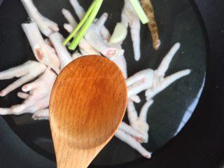 红烧鸡爪,锅里放适量的清水,放入鸡爪,放入一瓣蒜,一片姜片,一小段大葱,2勺料酒。 开火,水开后煮3~5分钟。