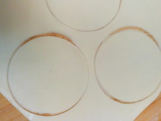 柴犬豆沙包,把白色面团擀成薄片,用杯子口或模具割出圆形。