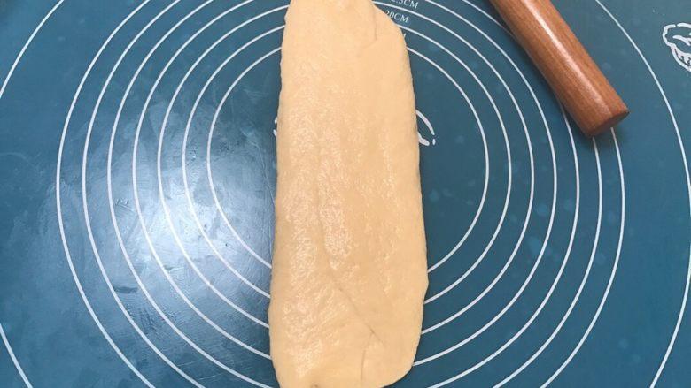 全中种北海道土司,取一个松弛好的面团再次擀成长舌头状,比之前的要窄一些