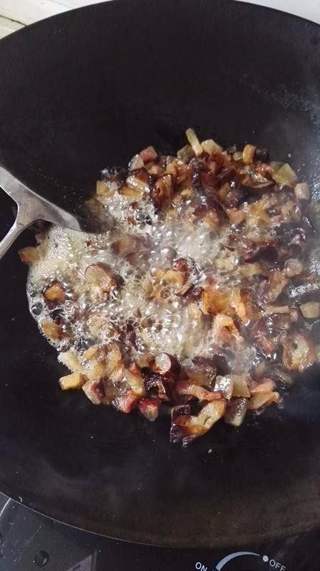 侗家社饭的做法,腊肉里的瘦肉挑出来,以免炒久变糊。然后放少许菜籽油,等油熬好,没有气泡后,把肥腊肉和腊肠一起炒,等炒出油来,锅里冒出很多油的泡沫后,再放下瘦