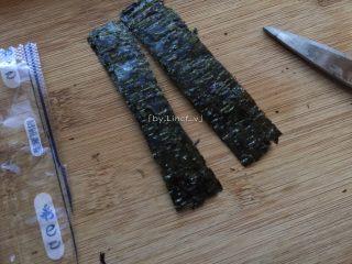 寿司玉子烧,放凉玉子烧的时间里可以先准备好海苔。将即食海苔用剪刀沿竖向中间剪开,分成两半的小长条状