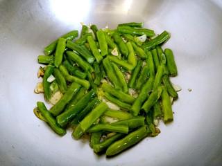 干煸四季豆,倒入四季豆,用铲子炒均匀后铺平,为了使每个四季豆均匀受热。