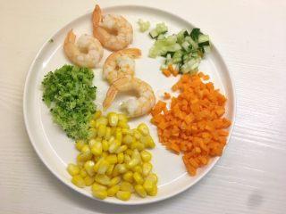 凤尾虾饭团,将胡萝卜、黄瓜切成丁,玉米剥粒,西兰花切碎