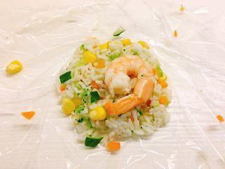 凤尾虾饭团,取一张保鲜膜,舀一勺饭,再放一个虾在饭的中间