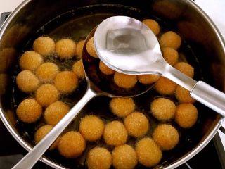 南瓜麻团,麻团飘起来后,用漏勺捞起后用勺子轻按压2-3下,然后放入锅内继续油炸