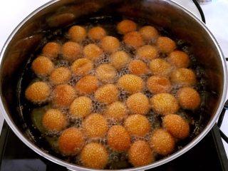 南瓜麻团,把锅内的油继续加热后再加入麻团,炸制麻团金黄即可