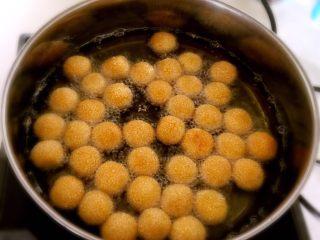 南瓜麻团,锅底加入大豆色拉油,油温5分热的时候加入麻团,温火炸制