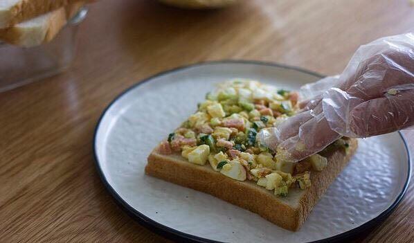 快手美味鸡蛋三明治,取一个面包片,把馅料放在上面,压实以后再加一层。可以加上喜欢的<a style='color:red;display:inline-block;' href='/shicai/ 121'>生菜</a>。