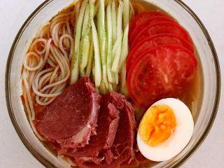 捞汁莜面,在泡好的一莜面上放入瓜丝,牛肉,西红柿勺,熟鸡蛋,浇上调好的汤汁