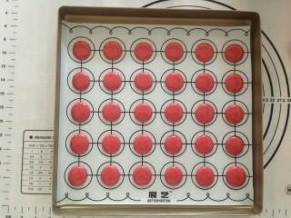 面粉版马卡龙,在马卡龙垫上垂直挤出圆形,挤好后,将烤盘从离台面十多公分处,垂直向下震出气泡。