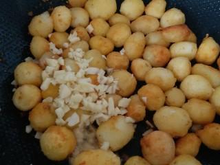 万能的土豆+飘香小土豆,土豆呈金黄色,加入大蒜粒炒均匀