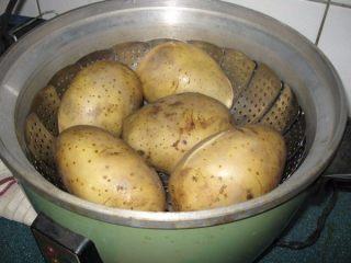 孜然土豆,土豆用电饭锅蒸至8分熟。土豆用一杯水下去蒸至跳起,就大约是8分熟,里面还会有点微硬。(如果不用电饭锅,可以水煮十几分。)