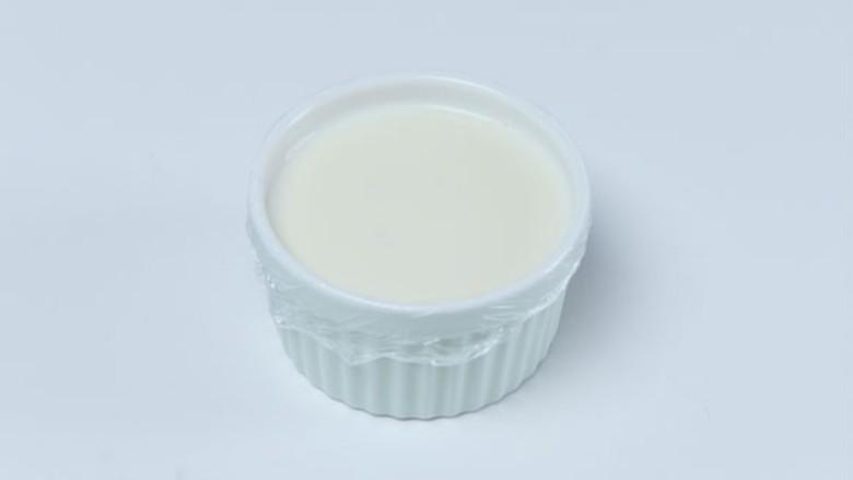 双皮奶,倒入小碗中,盖上保鲜膜,用牙签在保鲜膜表面扎几个小洞