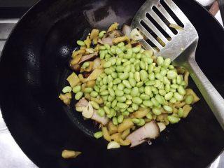 萝卜干毛豆炒腊肉,接着放入毛豆,翻炒均匀。