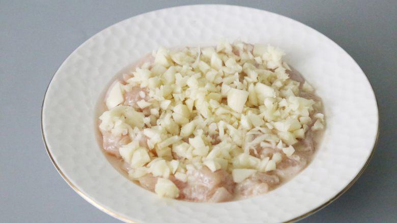 蒜蓉鸡胸肉,腌制好的鸡胸肉放入一个盘子里铺平,撒上蒜末。
