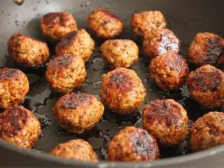 奇亚籽猪肉丸配生姜酱油汁,把酱汁倒入大号不粘锅中,中火加热,烧热后,加入肉丸,使其均匀裹上酱汁。