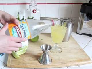 百里香莫吉托,充分摇晃,把调好的酒过滤到玻璃杯中,倒上橙子汽水 。