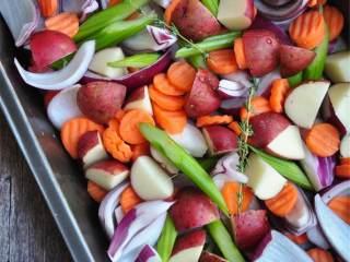 加勒比风情烤鸡配蔬菜,准备一个23厘米*33厘米的烤盘,底部铺上胡萝卜 、中等大小的红洋葱 、红皮土豆块 和芹菜