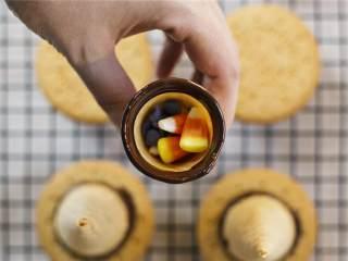 女巫帽子饼干,迅速在蛋筒里放入万圣节糖果 ,利用巧克力将蛋筒与饼干粘在一起,放为冷晾架。