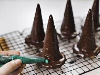 女巫帽子饼干,根据产品说明,将绿色糖果融化,装在一次性的裱花袋里,用剪刀将头剪开,小心地给帽子镶上边。